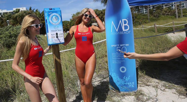 aroline Oliveira (L) and Rachel Scherdin help unveil one of 50 sunscreen dispensers that are being setup along the beach on March 13, 2015 in Miami Beach, Florida.