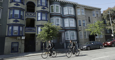 Bicyclists ride past a multi-unit property, at center, where a woman was charged with murder in the slaying of her roommate in San Francisco, Thursday, June 7, 2018. A dismembered body was discovered in oozing plastic bags inside a maggot-filled storage c