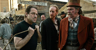 "In this Feb. 9, 2005 file photo, David Milch, left, creator of the HBO series ""Deadwood,"" appears on the set with Larry Cedar, center, and Peter Jason in Santa Clarita, Calif. HBO says it's greenlighted a long-discussed movie based on the Western drama th"
