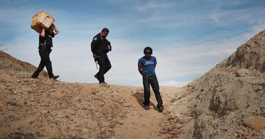 A migrant is taken into custody by Mexican police