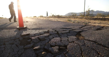 People walk near cracks in the road after a 6.4 magnitude earthquake struck the area on July 4, 2019 near Ridgecrest, California.