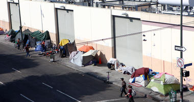 People walk past a homeless tent encampment in Skid Row on September 16, 2019 in Los Angeles, California.