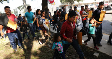 Dozens of women, men and their children, many fleeing poverty and violence in Honduras, Guatamala and El Salvador, arrive at a bus station following release from Customs and Border Protection on June 23, 2018 in McAllen, Texas.
