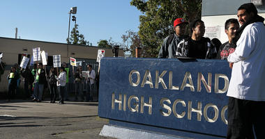 Students look on as teachers hold signs while they protest during a one-day strike outside of Oakland High School April 29, 2010 in Oakland, California.