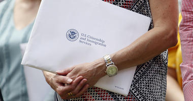 Jun 27, 2019; Detroit, MI, USA; A woman holds her citizenship paperwork before the game between the Detroit Tigers and the Texas Rangers at Comerica Park.