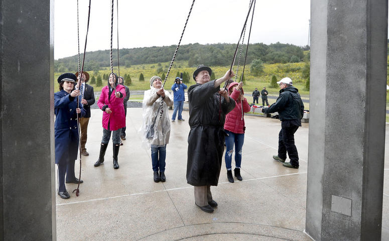 Members of passenger families, friends and volunteer repesentatives pull the ropes to ring the chimes at the dedication of the 93-foot tall Tower of Voices