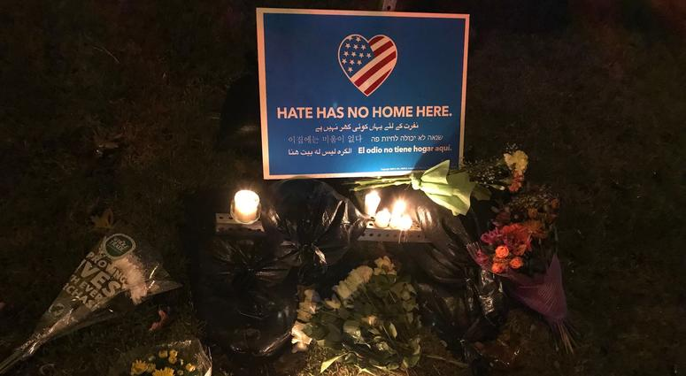 """flowers and candles beneath a sign that reads """"Hate has no home here."""""""