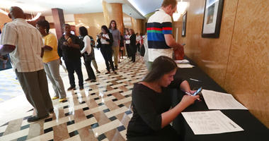 Emily Esparza, lower right, fills out a questionnaire as other job applicants line up at the Seminole Hard Rock Hotel & Casino Hollywood during a job fair in Hollywood, Fla. On Friday, July 5, the U.S. government issues the June jobs report.
