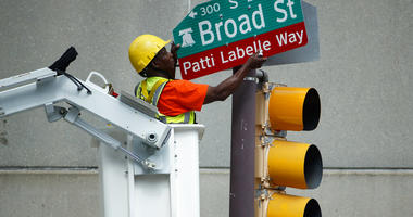 "A worker hangs a street sign before a ceremony honoring singer Patti LaBelle, Tuesday, July 2, 2019, in Philadelphia. A stretch of Broad Street, between Locust and Spruce Streets, will be renamed ""Patti LaBelle Way."""