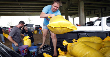 Tiffany Delee tosses a filled sandbag into the back of the family truck, while her husband Mike Delee, left, readies to tie up another bag, in Morgan City, La., Friday, July 12, 2019. The Delee's will use the bags to help protect their grandmother's house