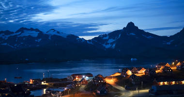 homes are illuminated after the sunset in Tasiilaq, Greenland. (