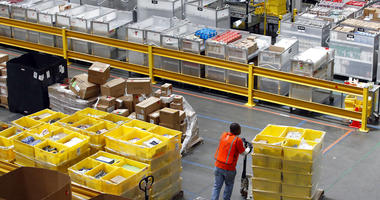 a worker pushes bins at an Amazon fulfillment center in Baltimore.