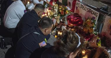Emergency responders pay their respect, joining thousands of mourners contribute candles, notes, flowers, and prayer to the spreading memorial at the Cielo Vista Walmart