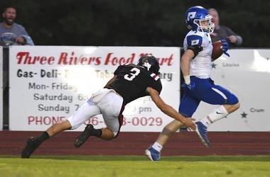 Paintsville's John Walker Phelps on a 44-yard touchdown run past Lawrence County's Andrew Tackett on Friday, Aug. 23, 2019 in Louisa, Ky. Paintsville won 48-17.