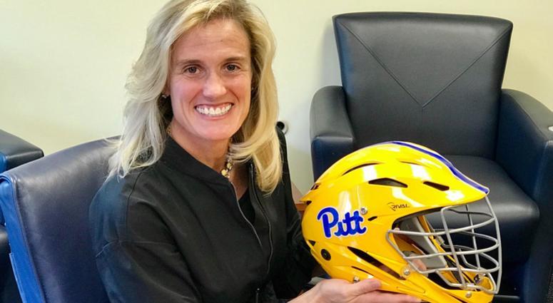 Pitt AD Heather Lyke with women's lacrosse goalie helmet in 2018