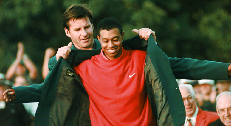 Masters champion Tiger Woods receives his Green Jacket from last year's winner Nick Faldo, rear, at the Augusta National Golf Club in Augusta, Ga. Woods completes an amazing journey by winning the 2019 Masters, overcoming 11 years of personal foibles and
