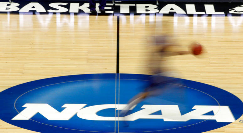 a player runs across the NCAA logo during practice at the NCAA tournament college basketball in Pittsburgh
