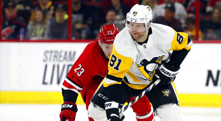 Pittsburgh Penguins' Phil Kessel (81) takes the puck away from Carolina Hurricanes' Brock McGinn (23) during the first period of an NHL hockey game, Tuesday, March 19, 2019, in Raleigh, N.C.