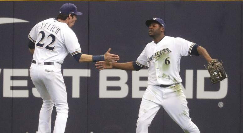 Milwaukee Brewers' Lorenzo Cain is congratulated by Christian Yelich after catching a ball at the wall hit by St. Louis Cardinals' Jose Martinez during the ninth inning of an Opening Day baseball game Thursday, March 28, 2019, in Milwaukee.
