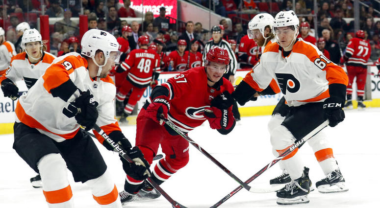 Philadelphia Flyers' Ivan Provorov (9) of Russia and Philippe Myers (61) battle Carolina Hurricanes' Andrei Svechnikov (37) of Russia for the puck during the third period of an NHL hockey game in Raleigh, N.C. on Saturday, March 30, 2019.