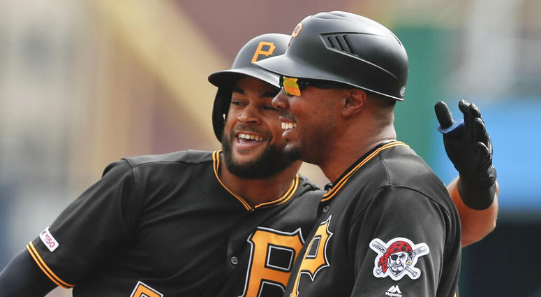 Pittsburgh Pirates Jason Martin, left, puts his arm around first base coach Kimera Bartee after getting his first major league hit off Cincinnati Reds starting pitcher Tanner Roark in the first inning of a baseball game, Saturday, April 6, 2019, in Pittsb