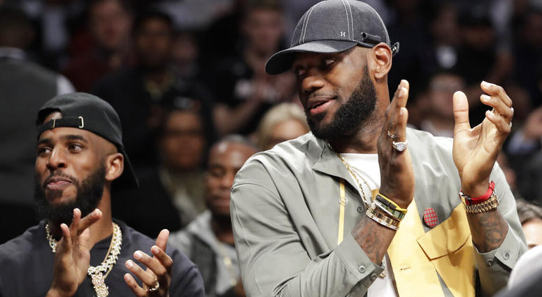 Chris Paul and LeBron James applaud during a ceremony at an NBA basketball game between the Brooklyn Nets and the Miami Heat, Wednesday, April 10, 2019, in New York. The pair were there to watch Heat guard Dwyane Wade play his last NBA game