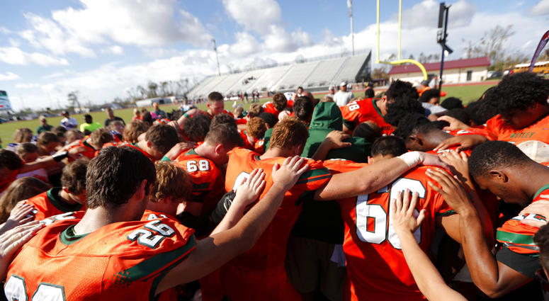 Coaches and players from Mosley High pray together after their loss to Pensacola High