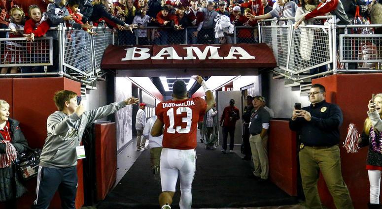Alabama quarterback Tua Tagovailoa (13) waves to fans as he runs off the field