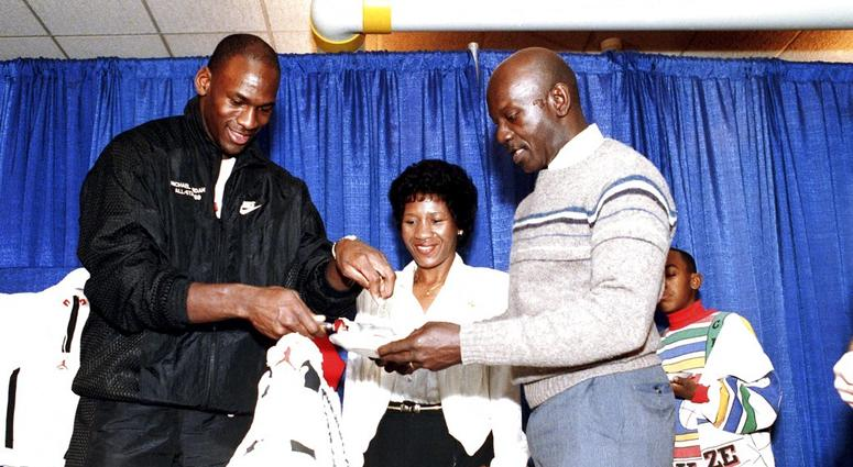Chicago Bulls' Michael Jordan serves his father, James, a slice of birthday cake as his mother, Doloris, watches during a party in honor of Jordan's 26th birthday in Chicago, Ill.