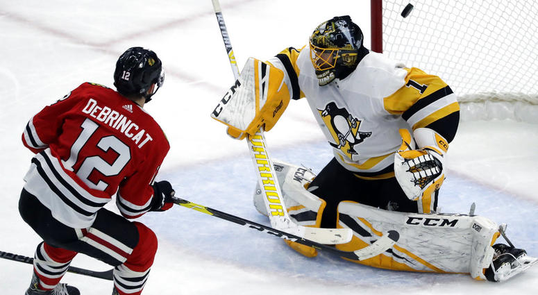 Chicago Blackhawks left wing Alex DeBrincat, left, scores against Pittsburgh Penguins goalie Casey DeSmith
