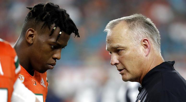 Miami quarterback N'Kosi Perry, left, talking with Miami head coach Mark Richt