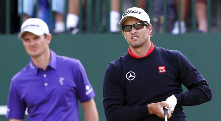 Adam Scott, of Australia, watches his shot off the first tee with Justin Rose, of England