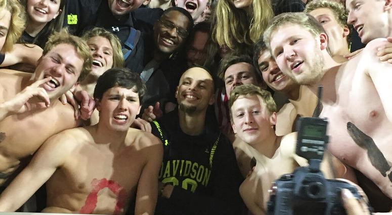 Golden State Warriors' Stephen Curry, center, poses with the Davidson College swim team as he takes in an NCAA college basketball game at his alma mater Friday, Feb. 15, 2019, while back in his hometown of Charlotte, N.C., for the NBA basketball All-Star