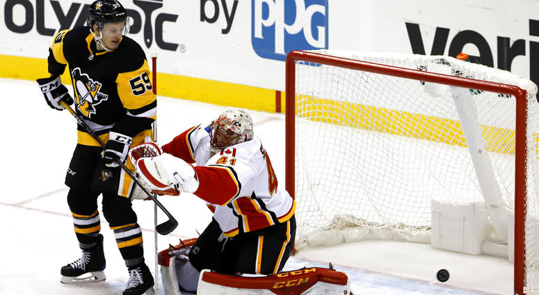 Pittsburgh Penguins' Jake Guentzel (59) defects the puck past Calgary Flames goaltender Mike Smith (41) for a goal in the first period of an NHL hockey game in Pittsburgh, Saturday, Feb. 16, 2019