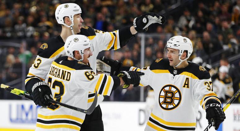 , Boston Bruins' Brad Marchand, front, celebrates with teammates Zdenoa Chara, back left, and Patrice Bergeron