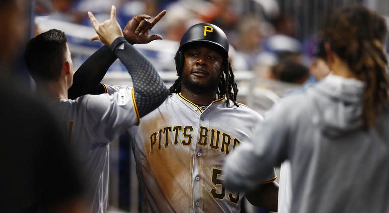 Pittsburgh Pirates' Josh Bell (55) celebrates in the dugout after scoring during the fifth inning of a baseball game against the Miami Marlins, Friday, June 14, 2019, in Miami.