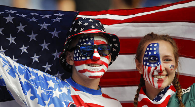 Austin, left, and Jordyn Chambers, from Philadelphia, hold up an US flag prior the Women's World Cup Group F soccer match between United States and Chile at Parc des Princes in Paris, France, Sunday, June 16, 2019.