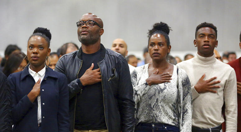"""Mixed martial arts great Anderson """"Spider"""" Silva of Brazil, his daughter Kaory, 23, left, his wife Dayane and son Kalyl, 20, right, recite the Pledge of Allegiance after all but Dayane were sworn in as U.S. citizens in a mass naturalization ceremony Tuesd"""