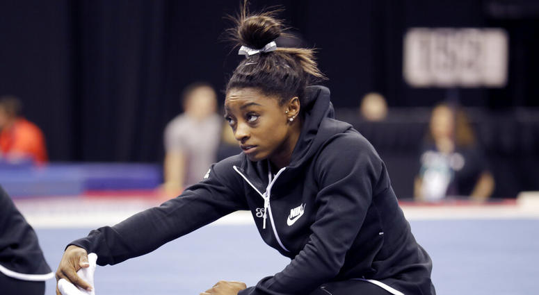 Simone Biles stretches during practice for the U.S. Gymnastics Championships Wednesday, Aug. 7, 2019, in Kansas City, Mo.