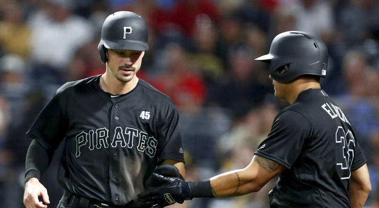 Pittsburgh Pirates' Bryan Reynolds, left, is greeted by on-deck batter Jose Osuna after scoring on a groundout by Colin Moran during the sixth inning of the team's baseball game against the Cincinnati Reds, Friday, Aug. 23, 2019, in Pittsburgh.