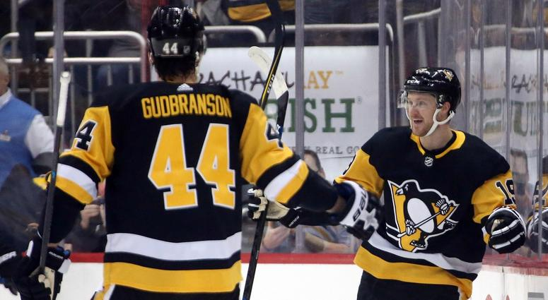 Pittsburgh Penguins center Jared McCann (19) reacts after scoring a goal with Pittsburgh Penguins defenseman Erik Gudbranson (44) against the Boston Bruins during the first period at PPG PAINTS Arena.