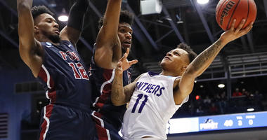 Prairie View A&M's Dennis Jones (11) shoots against Fairleigh Dickinson's Mike Holloway Jr., center, and Kaleb Bishop (12) during the second half of a First Four game of the NCAA college basketball tournament, Tuesday, March 19, 2019, in Dayton, Ohio