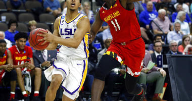 LSU's Tremont Waters, left, goes to the basket past Maryland's Darryl Morsell (11) during the first half of a second-round game in the NCAA men's college basketball tournament in Jacksonville, Fla., Saturday, March 23, 2019