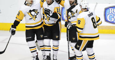 Pittsburgh Penguins center Jared McCann (19) is congratulated for scoring a goal with teammates Teddy Blueger (53), Kris Letang (58), Brian Dumoulin (8) during the second period of an NHL hockey game against the Dallas Stars in Dallas, Saturday, March 23,