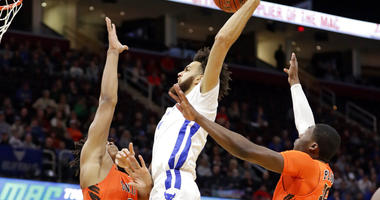 Buffalo's Jeremy Harris, center, drives to the basket against Bowling Green's Demajeo Wiggins, left, and Daeqwon Plowden during the first half of an NCAA college basketball championship game of the Mid-American Conference men's tournament, Saturday, March