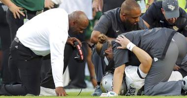 South Florida coach Charlie Strong, left, comforts Central Florida quarterback McKenzie Milton