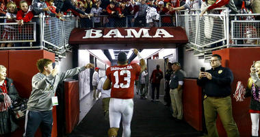 Alabama quarterback Tua Tagovailoa (13) waves to fans as he runs off the field