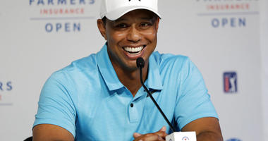 Tiger Woods laughs during a news conference after finishing on the north course at Torrey Pines Golf Course during the pro-am event at the Farmers Insurance Open golf tournament, in San Diego