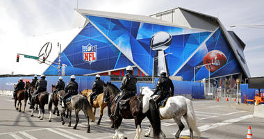 Police on horseback patrol past Mercedes-Benz Stadium ahead of Sunday's NFL Super Bowl 53 football game between the Los Angeles Rams and New England Patriots in Atlanta
