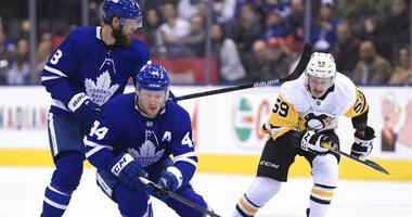 Toronto Maple Leafs defenseman Morgan Rielly (44) controls the puck as teammate Jake Muzzin (8) battles Pittsburgh Penguins left wing Jake Guentzel